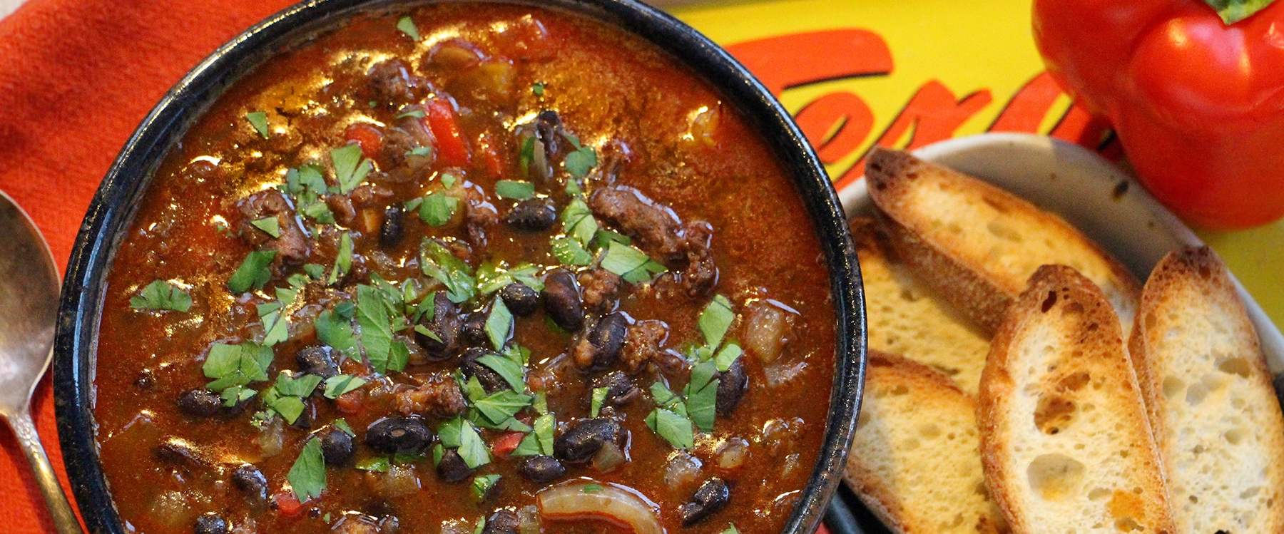 A bowl of black bean chorizo soup seasoned with JK's Seasoning with toasted bread.