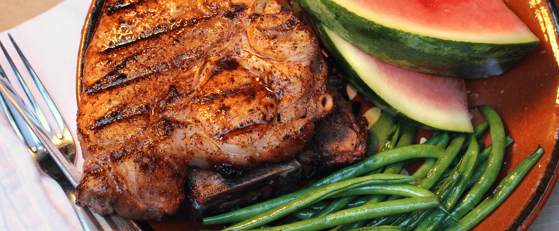 A plate of JK's seasoned pork porterhouse chop, green beans and watermelon slices.